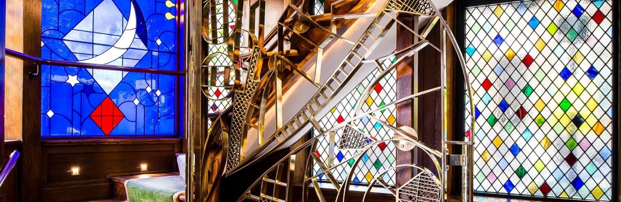 The stained glass windows and staircase at The Ivy West Street, near Leicester Square in London